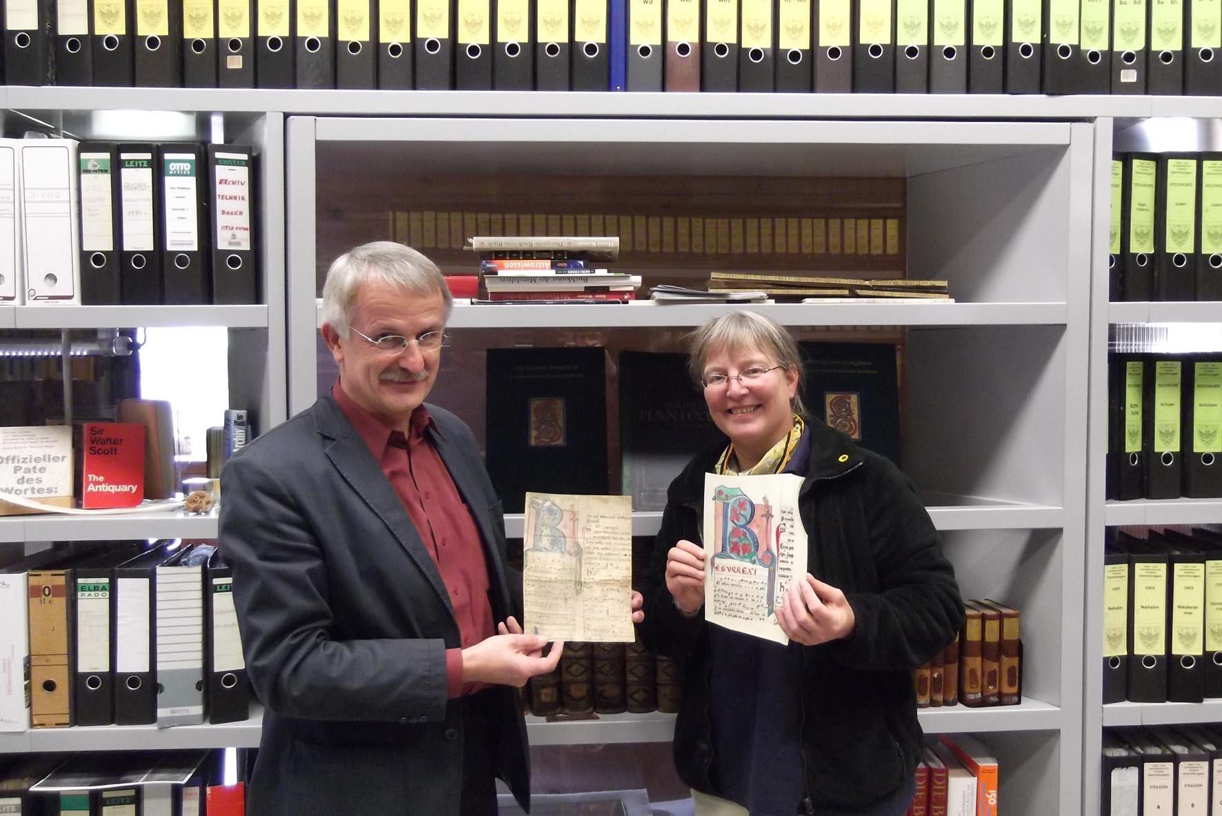 Die Kalligrafin Susanne Ulmke übergibt das Pergamentfaksimile an Stadtarchivar Michael Gosmann, der das Original in Händen hält. Foto: Nadja Töws, Stadtarchiv