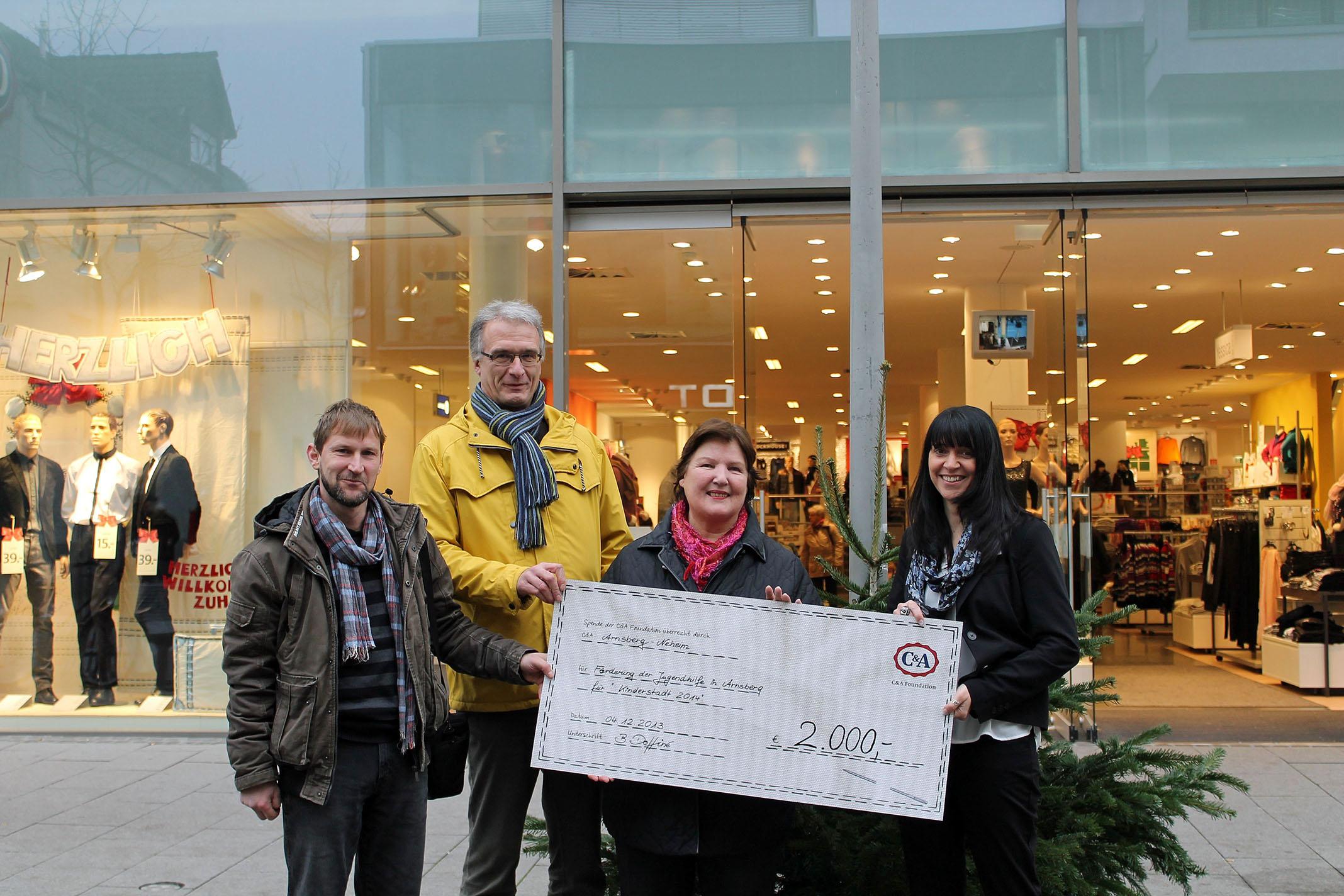 Die Übergabe des Spendenschecks für die Kinderstadt 2014 vor der C&A-Filiale in der Neheimer Fußgängerzone.