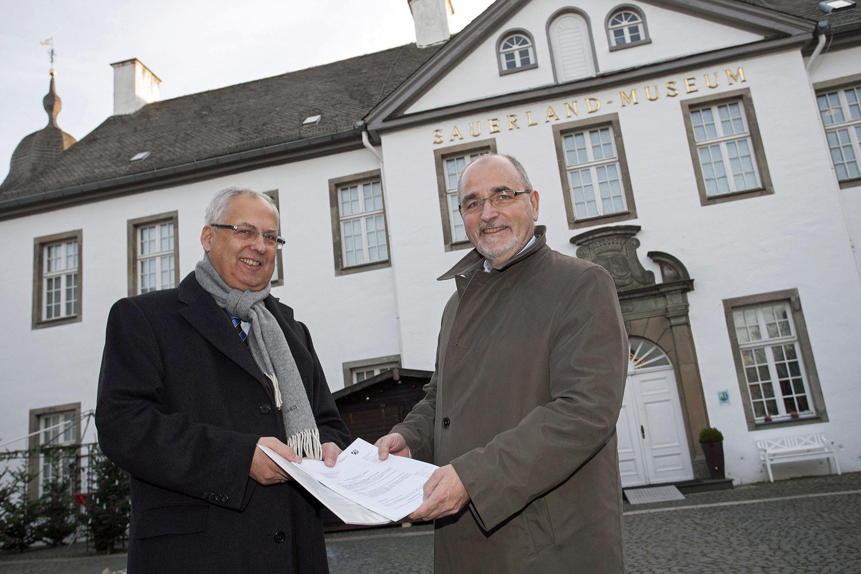 """RP Dr. Gerd Bollermann (r.) übergibt gleich zwei millionenschwere Förderbescheide für das Regionale-Projekt """"Museums- und Kulturforum Südwestfalen"""" an HSK-Landrat Dr. Karl Schneider. (Foto: Bezirksregierung)"""