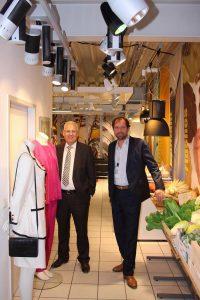 Umrahmt von Mode und Lebensmittelattrappen, die durch entsprechende Beleuchtung in Szene gesetzt werden: Landrat Dr. Karl Schneider (l.) und ELPRO-Juniorchef Kai K. Wiegelmann. / Foto: Pressestelle HSK