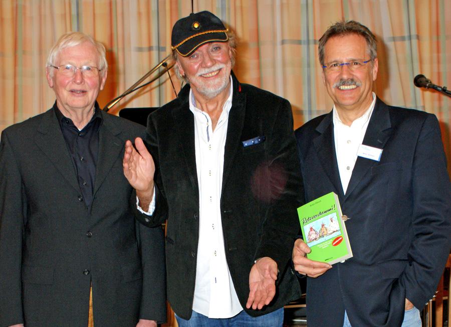 Willi Linn (SGV-Abt. Oeventrop, l.)) und Willy Verbanc (SGV-Abteilung Arnsberg, r.) holen Reiner Hänsch bereits zum dritten mal auf die Bühne des SGV-Jugendhofs. (Foto: Klaus Peters)